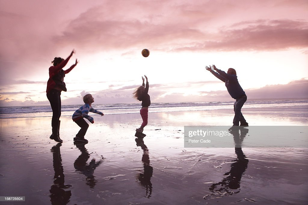 Family playing with ball on beach at sunset : Foto de stock