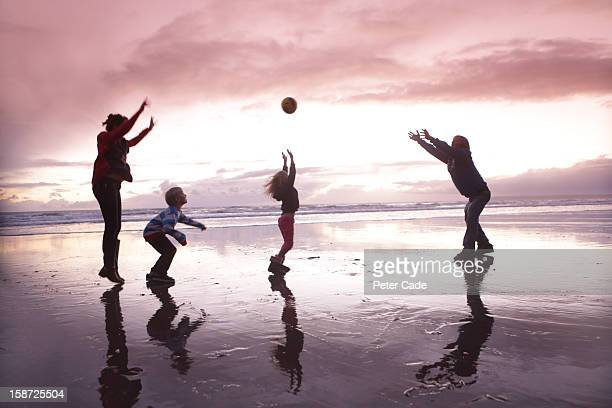 Family playing with ball on beach at sunset