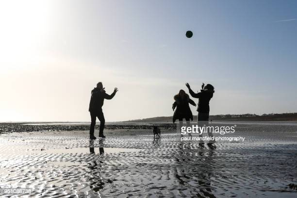 Family playing with ball on Worthing beach
