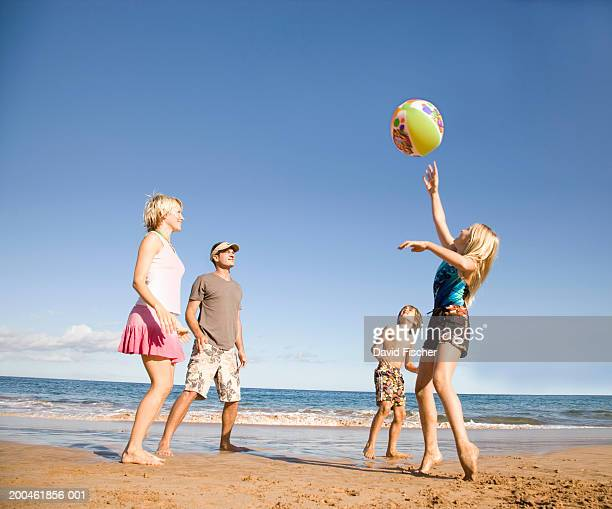 Family playing with beach ball on beach, low angle view