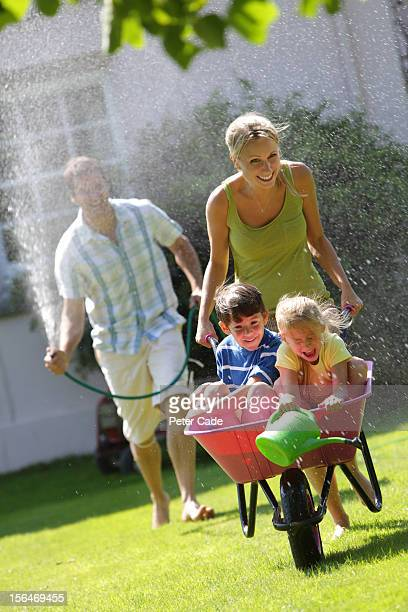 Family playing with hosepipe and wheelbarrow