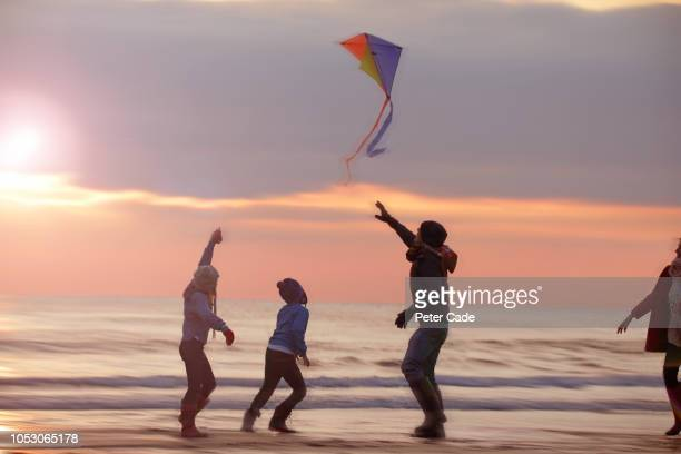 family playing with kite on beach at sunset - wind stock pictures, royalty-free photos & images