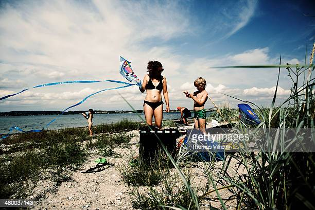 family playing with kites on the beach - funen stock pictures, royalty-free photos & images