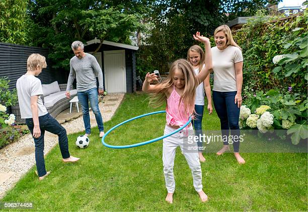 Family playing with the hula hoop outdoors