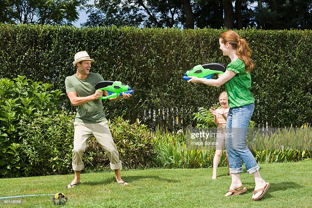 Family playing with water pistols : Stock Photo