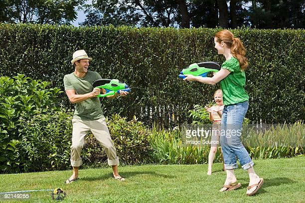 Famille, jouer avec des pistolets l'eau
