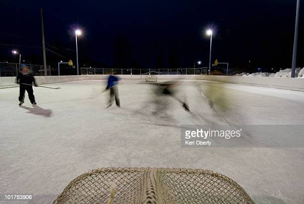 a family plays a game of pick-up hockey at the local elementary school's ice skating rink in anchorage, alaska. - アイスホッケー場 ストックフォトと画像