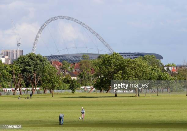 A family plays football in a park close to Wembley Stadium on what should have been FA Cup Final day on May 23 2020 in London England The British...