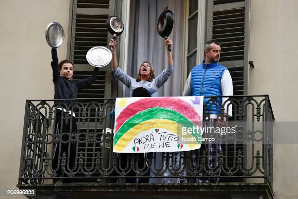 A family plays lids of pots and pans from balcony of their home where there is a banner reading 'Everything will be fine' in the neighborhood San...