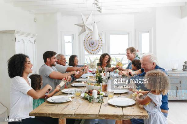 family popping christmas crackers together at dining table - lunch stock pictures, royalty-free photos & images