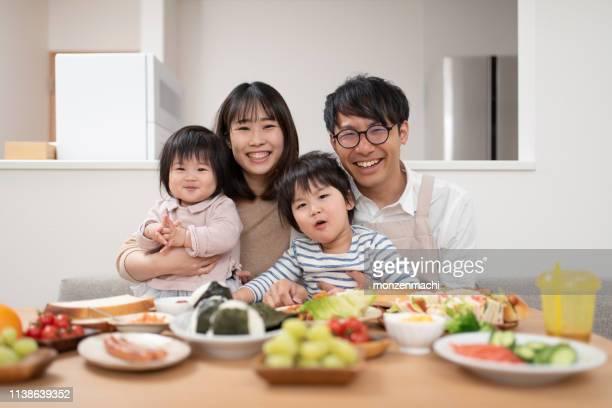 ダイニングルームでの家族の肖像 - 4人 ストックフォトと画像