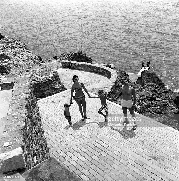 Family Portrait from Modugno in a swimsuit in a beautiful setting of sea and rocks from left the little Marcello the actress Franca Gandolfi the...