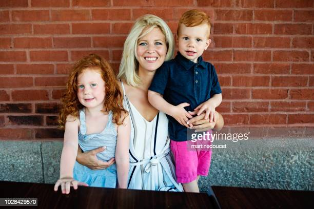 Family portrait of mother with redhead kids outdoors on a brick wall.