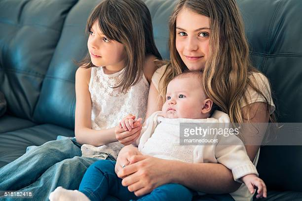 Family portrait of three sisters sitting on couch at home.