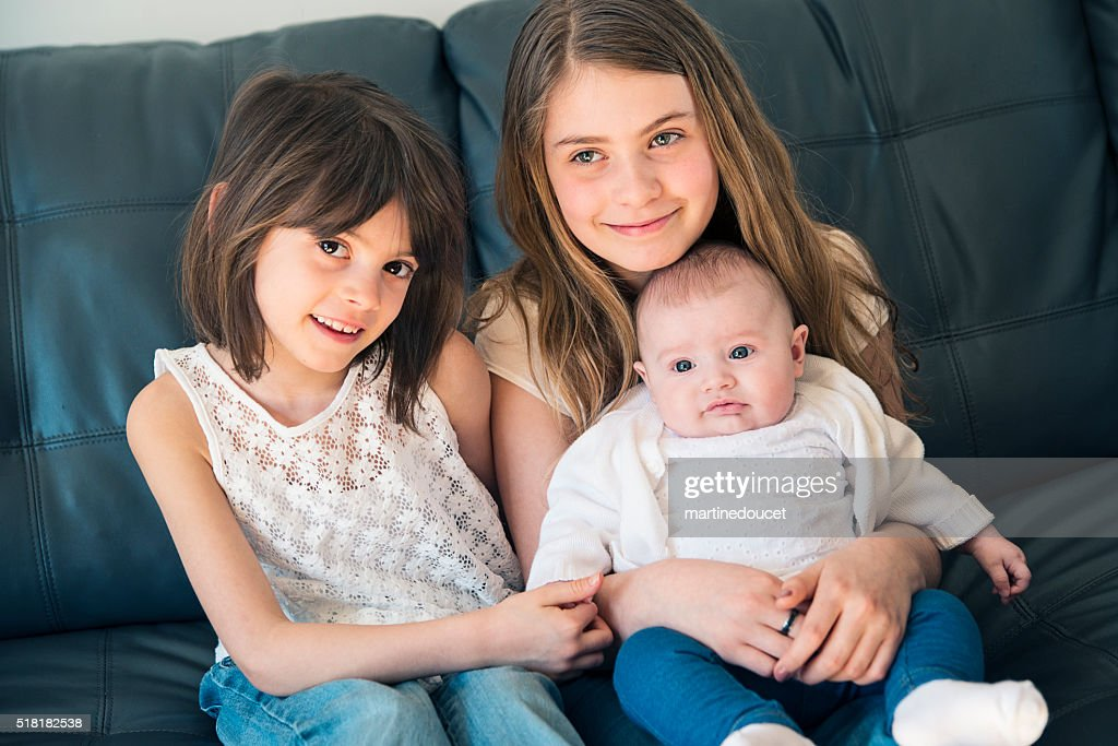 Family portrait of three sisters sitting on couch at home. : Stock Photo