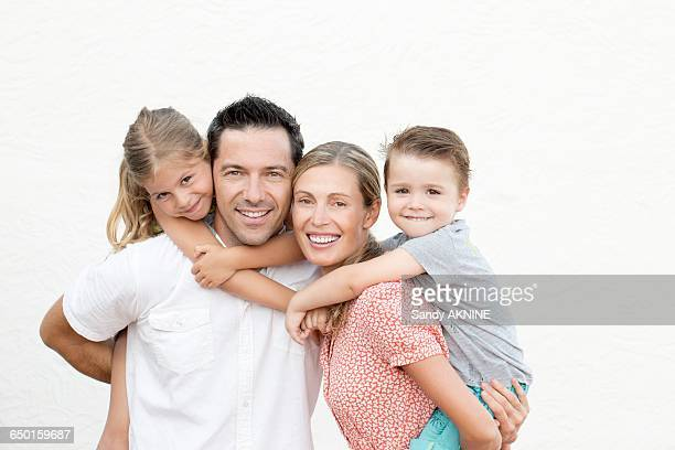 Family portrait, parents with their children on their back