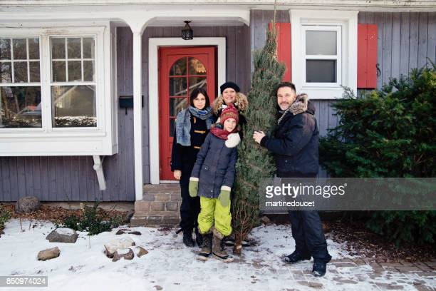 family portrait with freshly cut christmas tree in front of house outdoors. - 12 17 months stock pictures, royalty-free photos & images