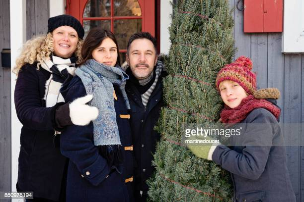 Family portrait with freshly cut Christmas tree in front of house outdoors.
