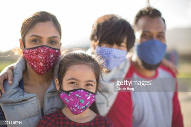family portrait with masks - travel stock pictures, royalty-free photos & images