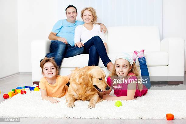 Family portrait with Retriever pet at home.