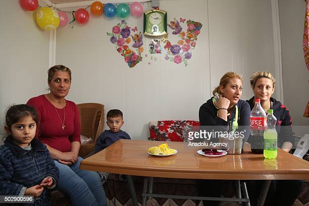 A family pose in a living room decorated with ballons ahead of the Christmas at the Bahirka Refugee Camp where Christian families from Mosul's...