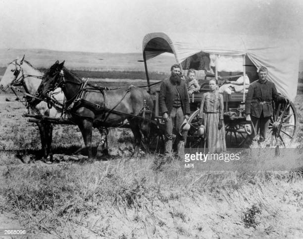 A family pose with their wagon in Loup Valley Nebraska on their way to their new homestead The Homestead Act of 1862 allowed any citizen over the age...