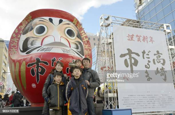 A family poses for a photo in front of a big 'daruma' a popular talisman of good luck at a daruma market in Takasaki Gunma Prefecture on Jan 2 2018...
