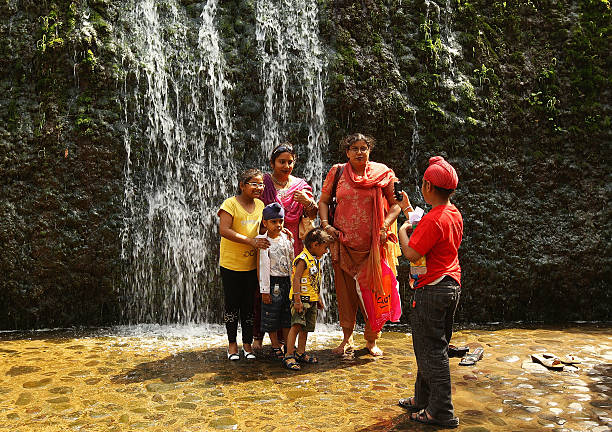 A family poses for a photo in front of a waterfall at the Rock Garden on March 26 2010 in Chandigarh India The 12acre Rock Garden which began as...