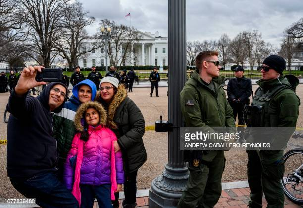 A family poses for a photo next to police monitoring a small group of Altright members holding a rally and counter protesters near the White House in...