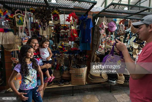 A family poses for a picture at the Adolpho Lisboa market in Manaus Brazil on November 26 2013 AFP PHOTO / YASUYOSHI CHIBA