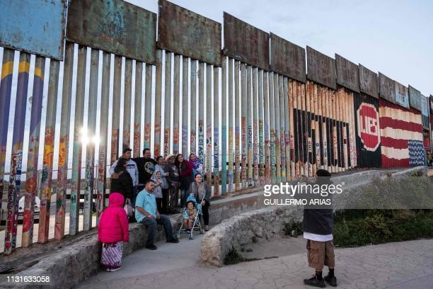 A family poses for a portrait at the USMexico border fence in Playas de Tijuana Baja California state Mexico on March 19 2019 Local media reported...