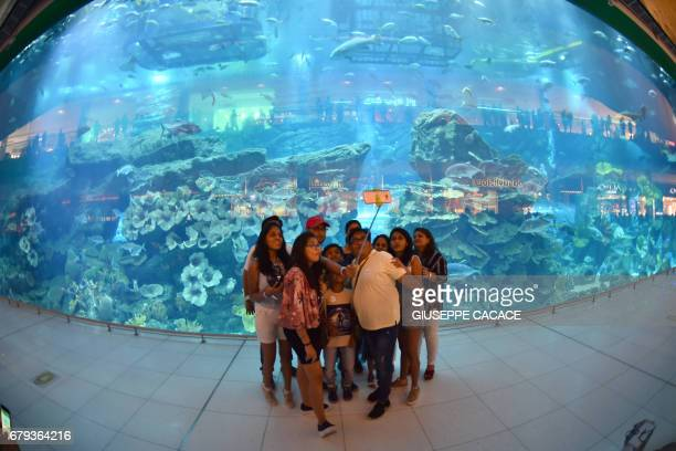 A family poses for a selfie in front of the Aquarium at Dubai Mall in Dubai on May 5 2017 / AFP PHOTO / GIUSEPPE CACACE