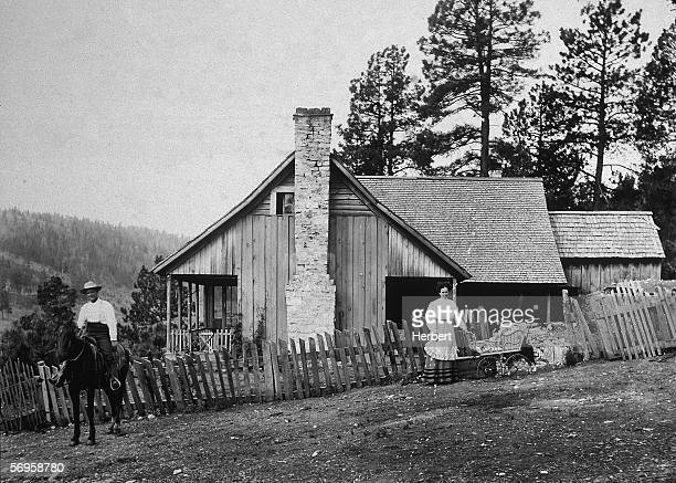 A family poses outside their house on their homestead Western US late 19th Century