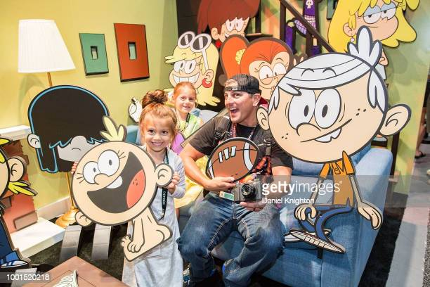 A family poses with props in a photo booth at the Nickelodeon booth during Preview Night at ComicCon International at San Diego Convention Center on...