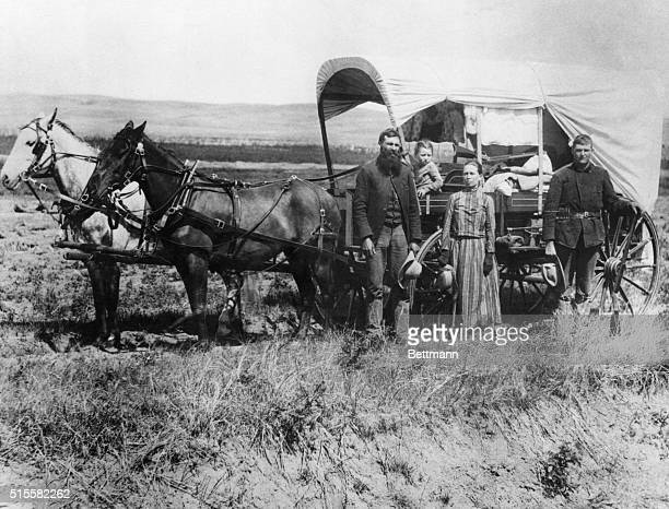 A family poses with the covered wagon in which they live and travel daily during their pursuit of a homestead Loup Valley Nebraska 1886 | Location...