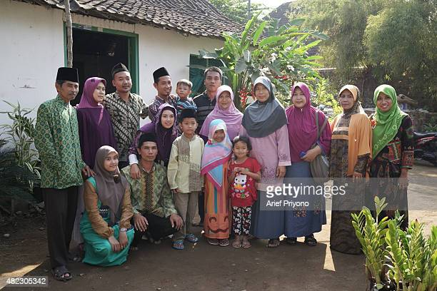 A family posing for a portrait photograph after the 'Ketupat Feast' in the village of Durenan Celebrating the 'Ketupat Feast' has been an annual...