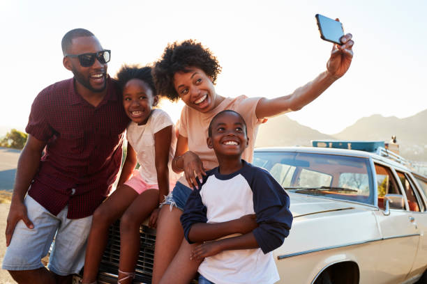 Family Posing For Selfie Next To Car Packed Road Trip