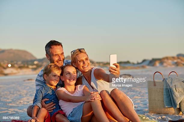 Family posing for selfie on beach