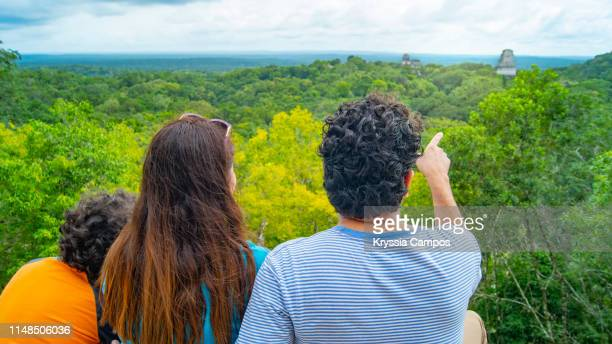 a family posing in front of rainforest and mayan pyramids in guatemala - guatemala stock-fotos und bilder