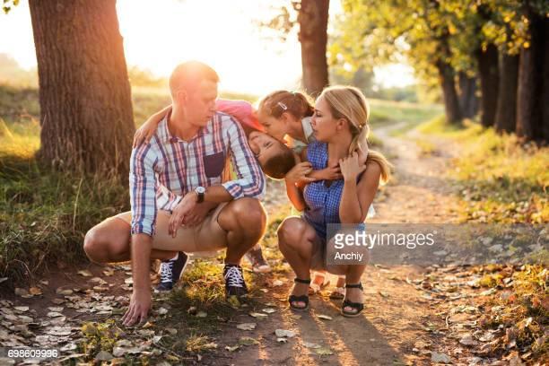 Familie poseren in het park. Schattig meisje kussen haar broer op een Wang.