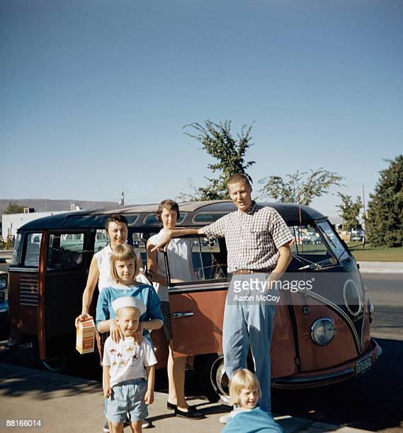 Family posing next to retro van