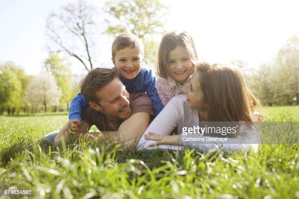 a family posing together in a park - lying on front stock pictures, royalty-free photos & images