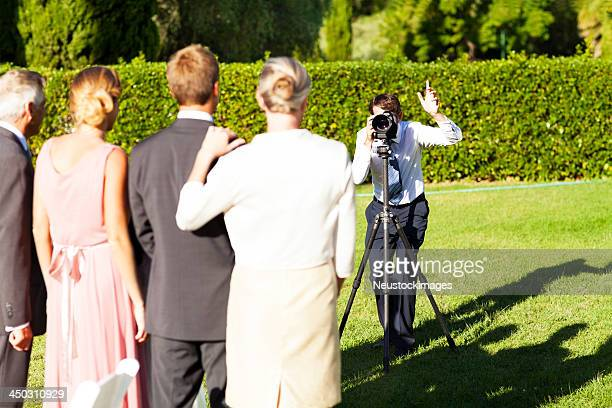 Family Posing While Man Photographing Them At Garden Wedding