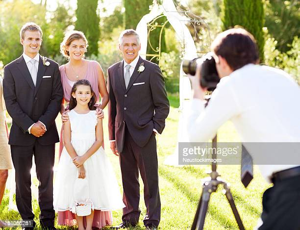 Family Posing While Man Photographing Them At Outdoor Wedding