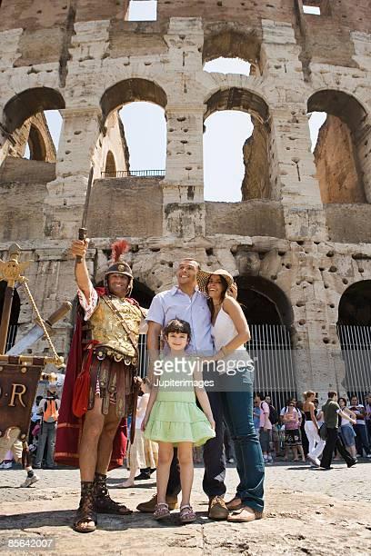 family posing with man in gladiator costume,  roman colosseum,  rome,  italy - gladiator stock-fotos und bilder