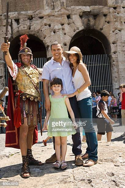 Family posing with man in gladiator costume,  Roman Colosseum,  Rome,  Italy