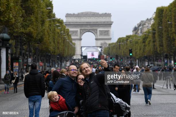 A family posses for a selfie photo along the Champs Elysees with the Arc de Triumph as a backdrop during a 'car free' day in Paris on October 1 2017...