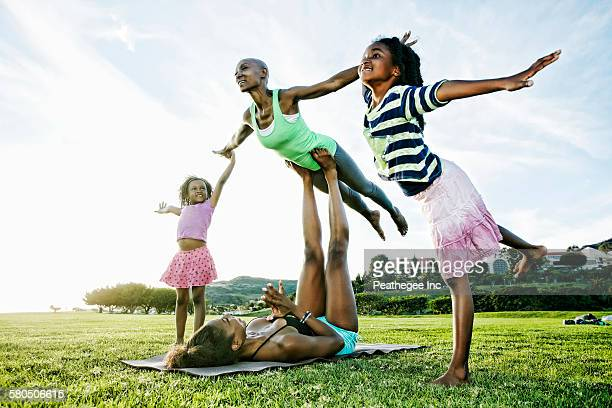 Family practicing acro yoga in park