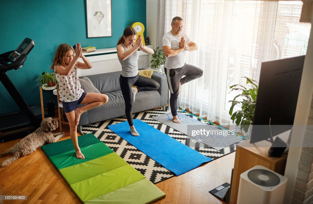 Family Practicing Yoga At Home With Online Classes : Stock Photo