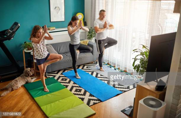 family practicing yoga at home with online classes - recreational pursuit stock pictures, royalty-free photos & images
